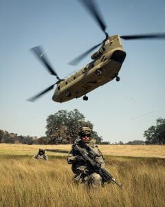 Pvt. Steven Diaz, Bravo Battery, 1-143rd Field Artillery, pulls LZ security as a CH-47F Chinook from 1-126th Aviation takes off after sling loading an M119A3 105mm Howitzer and his unit at Fort Hunter Liggett, Calif., June 15, 2015. (U.S. Army photo by Capt. Cody Gallo)