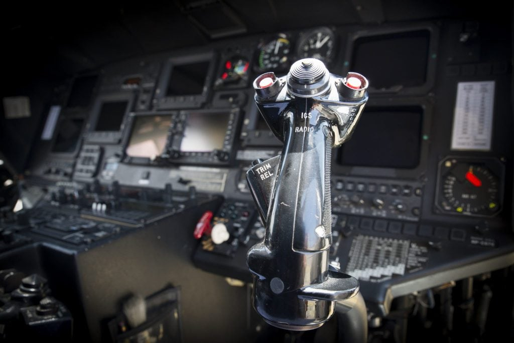 Inside a twin-engine helicopter cockpit showing modern dashboard and cyclic control stick.