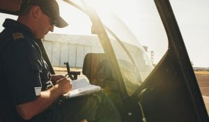Helicopter pilot checking the flight manual before a take off. Helicopter is on the ground with bright sunlight.
