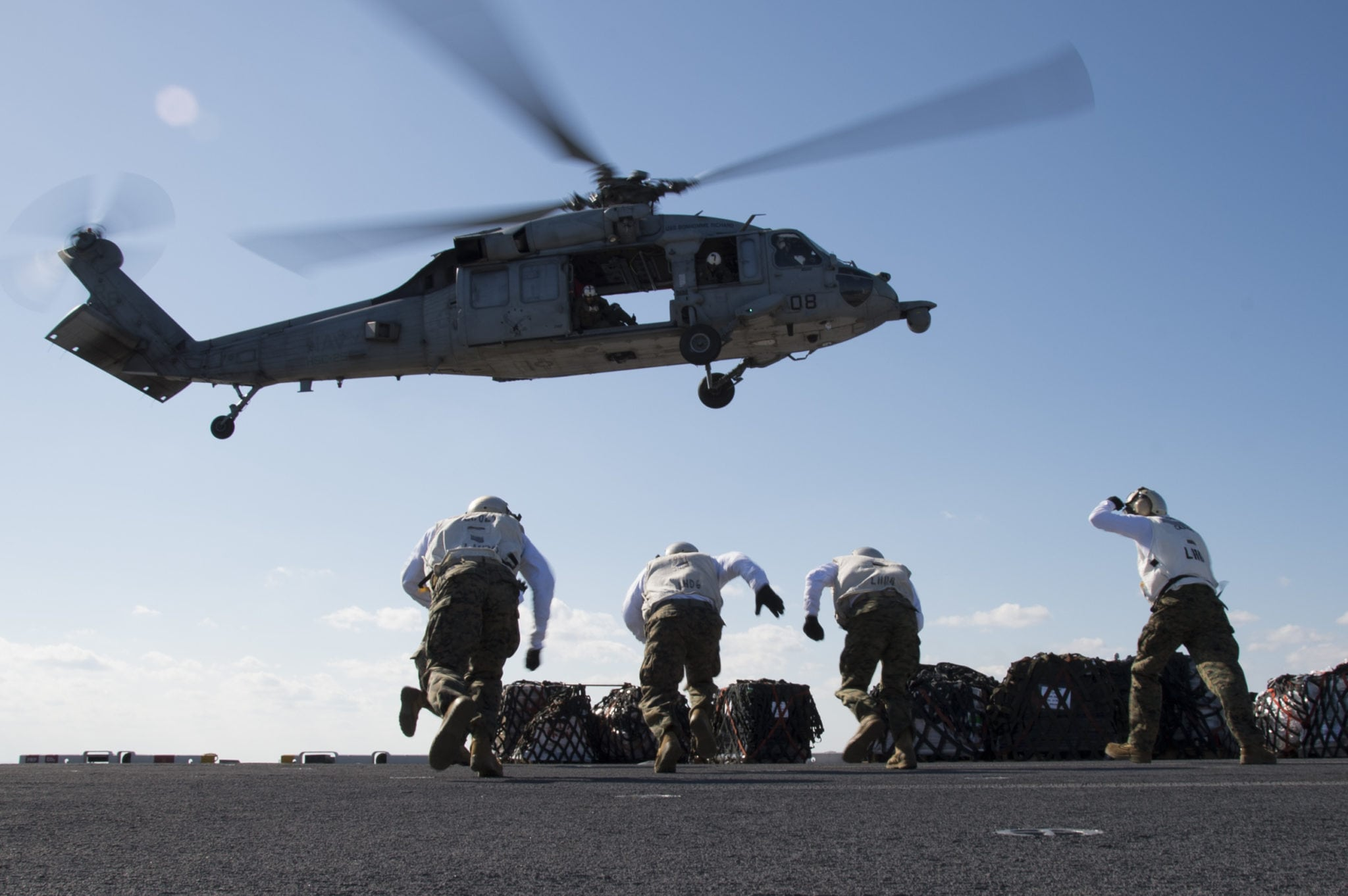 170228-N-XK809-250 EAST CHINA SEA (Feb. 28, 2017) Marines assigned to Combat Cargo receive supply pallets from an MH-60S Sea Hawk, assigned to Helicopter Sea Combat Squadron (HSC) 25, on the flight deck of amphibious assault ship USS Bonhomme Richard (LHD 6) during a replenishment-at-sea (RAS) with the Henry J. Kaiser-class replenishment oiler USNS Pecos (T-AO 197). Bonhomme Richard is on a routine patrol, operating in the Indo-Asia-Pacific region to serve as a forward-capability for any type of contingency. (U.S. Navy photo by Mass Communication Specialist 3rd Class William Sykes/Released)