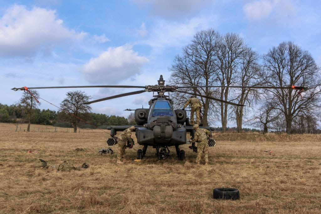 U.S. Soldiers assigned to 1st Battalion, 3rd Aviation Regiment (Attack Reconnaissance Battalion), 12th Combat Aviation Brigade, conduct routine maintenance on an AH-64 Apache attack helicopter during maneuvers training exercise at 7th Army Training Command's Grafenwoehr Training Area, Germany, March 15, 2017. (U.S. Army photo by Spc. Nathanael Mercado)