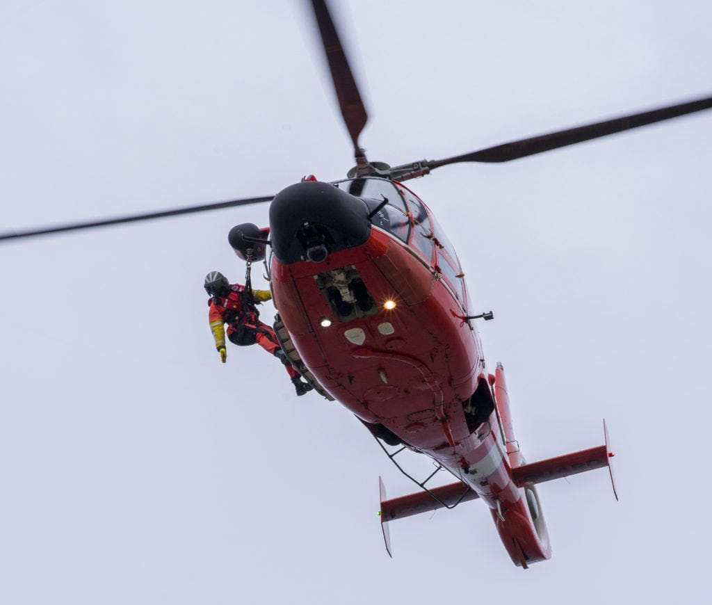 A rescue swimmer assigned to Coast Guard Forward Operating Base Point Mugu is lowered from an MH-65 Dolphin helicopter onto a cliff during rescue training at Point Vicente Lighthouse March 21, 2017. The training helps keep aircrews proficient in the event of a real world cliff side rescue. (U.S. Coast Guard photo by Petty Officer 3rd Class Andrea Anderson/Released)