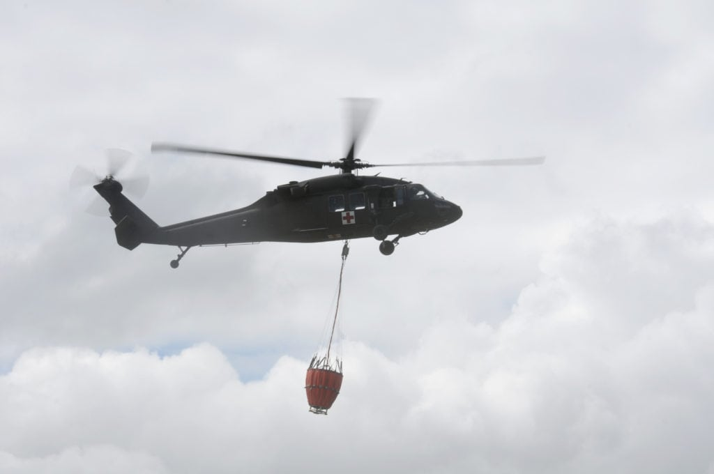 A UH-60 Black Hawk, assigned to the 1/189th, B-Company, General Support Aviation Battalion, Nevada Army National Guard, carries a basket of water to a simulated fire during a training event geared to prepare for fire season at Alpine County Airport, Calf. May 15, 2017. The Nevada Division of Forestry teamed up with the Nevada National Guard to organize the event. (U.S. Army National Guard photo by Sgt. Walter H. Lowell)