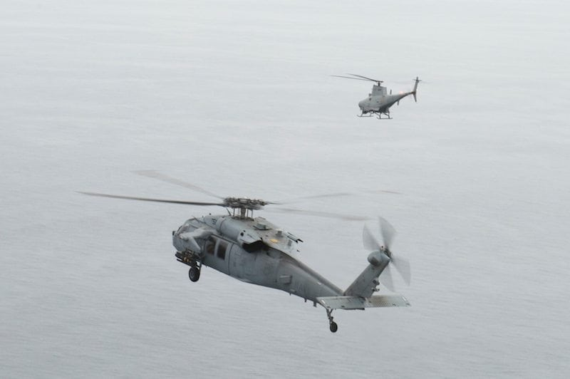 170510-N-FC195-112 PACIFIC OCEAN (May 10, 2017) An MQ-8B Fire Scout unmanned aerial vehicle, top, conducts laser designation of an AGM-114 Hellfire missile for an MH-60S Sea Hawk helicopter attached to the amphibious assault ship USS America (LHA 6) off the coast of San Clemente Island. Both Aircraft are operated by HSC-23, demonstrating the tactical application of integrated manned and unmanned platforms. (U.S. Navy photo by Mass Communication Specialist Third Class Trenton J. Kotlarz)