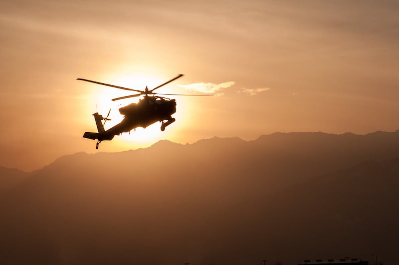 Pilots from 159th CAB, 101st Airborne Division, land an Apache helicopter at Bagram Air Field, Afghanistan, as the sun sets behind the mountains. (Photo by Chief Warrant Officer 2 George Chino)